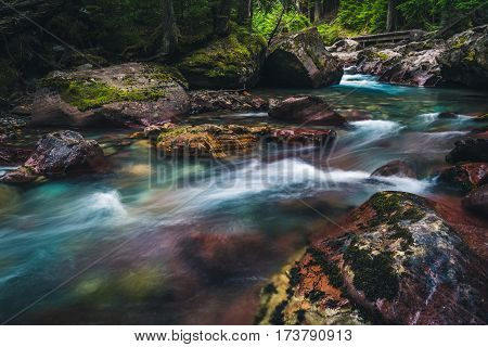 Image of a river flowing over a colorful riverbed.