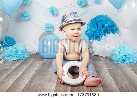 Portrait of cute adorable Caucasian baby boy with blue eyes barefoot in pants with suspenders and hat sitting on wooden floor in studio holding large letter O looking away first year concept