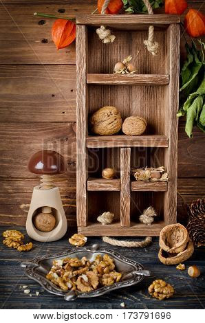 Still life with a wooden box and nuts. Vertical image