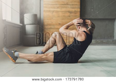 Young man workout in fitness club. Closeup portrait of caucasian guy making exercise, sit-ups and cross crunches for abs muscles, training indoors poster