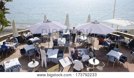 MARBELLA, SPAIN - FEBRUARY 26, 2017: People eating at the terrace of a restaurant close to the sea in Marbella Andalusia Spain