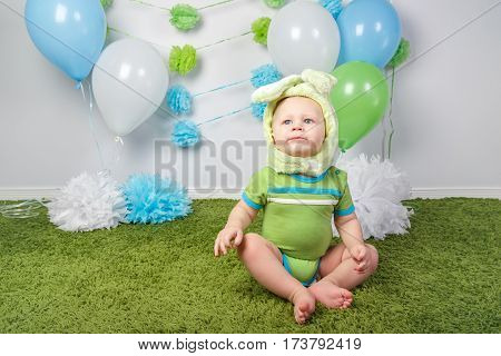 Portrait of cute adorable Caucasian baby boy in holiday Easter bunny rabbit costume with large ears dressed in green clothes onesie sitting on soft fluffy rug carpet in studio on white background