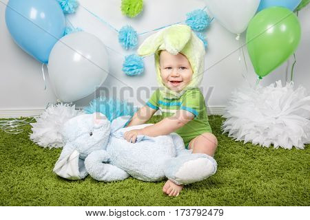Portrait of cute adorable Caucasian baby boy in holiday Easter bunny costume with large ears dressed in green clothes onesie sitting on soft fluffy rug carpet in studio holding rabbit toy