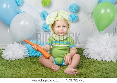 Portrait of cute adorable Caucasian baby boy in holiday Easter bunny rabbit costume with large ears dressed in green clothes onesie sitting on soft fluffy rug carpet in studio holding red carrot.
