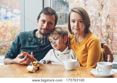 Portrait of white Caucasian happy family of three mother father and son sitting in restaurant cafe at table smiling playing authentic lifestyle
