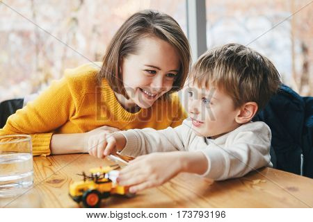 Portrait of white Caucasian happy family mother and son sitting in restaurant cafe at table smiling playing with toy car authentic lifestyle