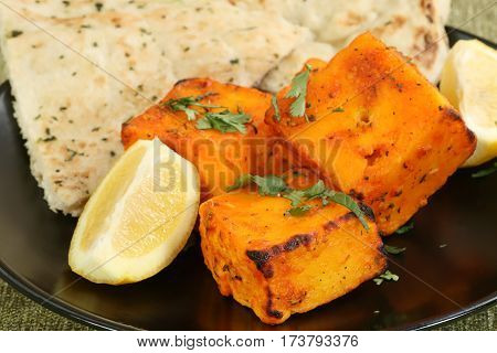 four pieces of marinated paneer cheese with coriander and lemon