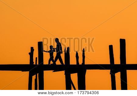 silhouette of father and son crossing the river on the longest bridge in the world, U-Bein bridge, Mandalay, Myanmar.