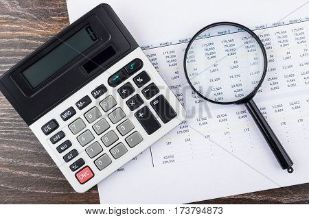 Printout, Electronic Calculator And Magnifying Glass On Wooden Table