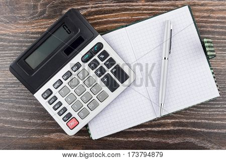 Open Notepad, Ballpoint Pen And Electronic Calculator On Table
