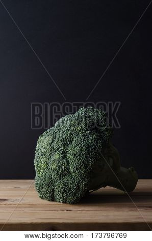 A head of dark green broccoli with stalk intact on wooden planked table against black chalkboard background. Moody lighting.