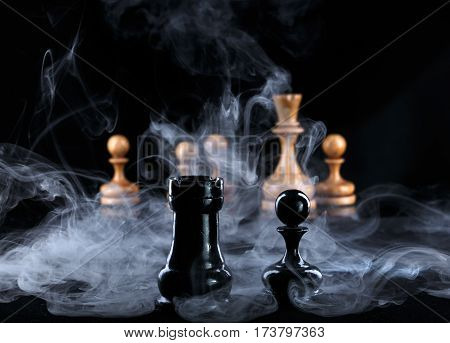 two black chess pieces in the fog opposite the white figures on black background