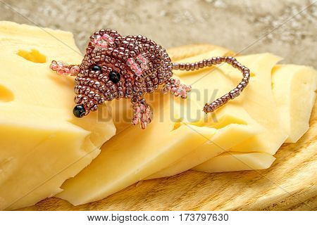 Mouse beaded toy sitting on a piece of real cheese.