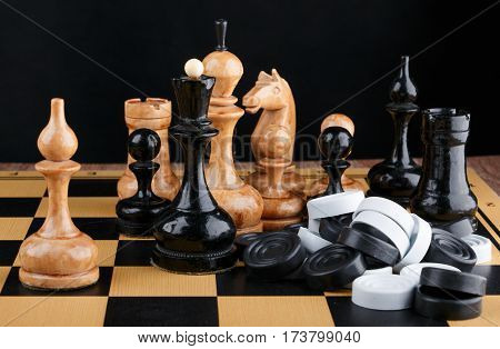 The chess pieces and pile of checkers placed on the chessboard. Black background