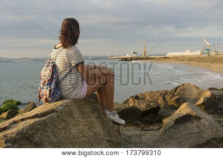 Summer vacation (a girl with a backpack, sitting on a rock on the seacoast)