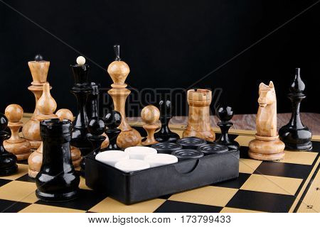 The chess pieces and set of checkers placed on the chessboard. Black background