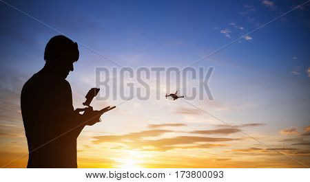 Drone pilot controling quadrocopter. Silhouette against the sunset sky.
