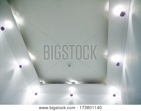 white ceiling with small round ceiling lamps and hidden ceiling light