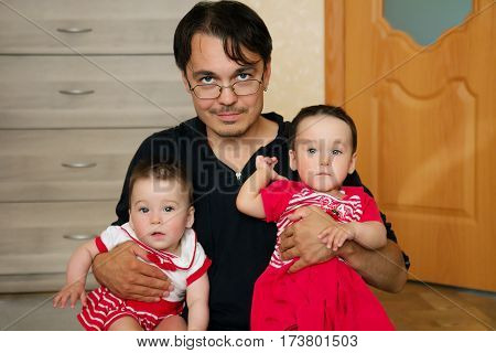 Happy young father with his twins kids pretty girls