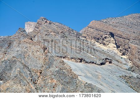 Mountain in oman showing strata of rocks in layers
