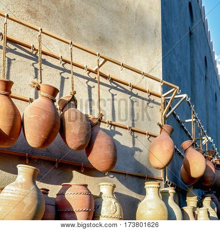 Earthenware pots hanging from ropes on display