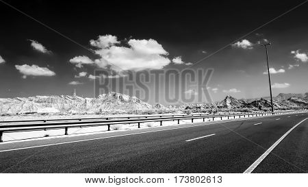 Infrared image of a asphalt road and a guardrail against a background of hills and a dark sky with clouds