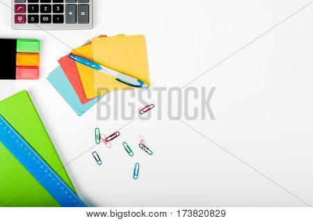 office school business education and technology concept - close up of notebook paper stickers pencil clip calculator different stuff on white background