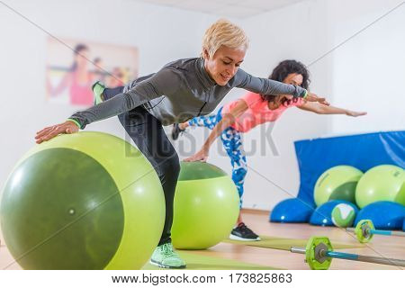 Fit Caucasian women doing crane exercise standing on one leg with their arms out to sides holding on to balance ball while training in fitness club.