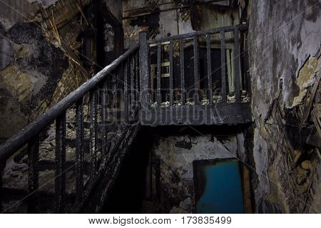 Interior of the burned by fire house, burned wooden stairs