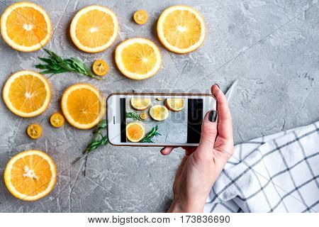 taking a photo with cell phone of sliced oranges on gray kitchen table background top view mock up