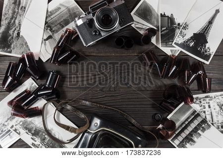 Old camera, film and black and white photographs are on the dark wooden surface. Retro. Top view