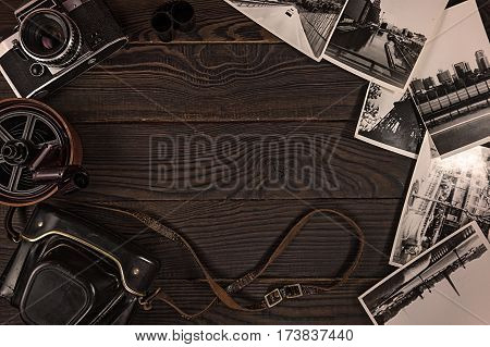Old camera, acsessories and black and white photographs are on the dark wooden surface. Retro. Top view