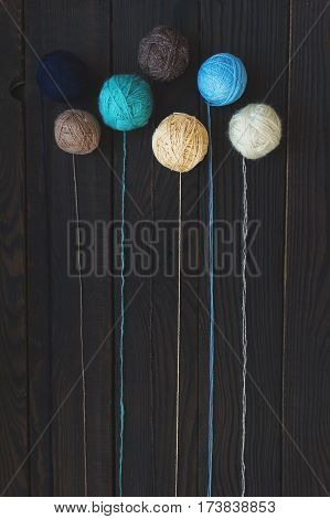 Five multicolored bolls of yarn on dark wooden surface. Top view