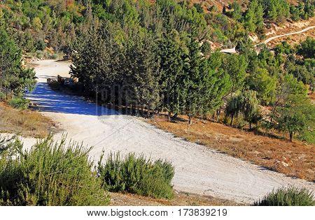 Rocky dirt road winding beside the Judean desert wilderness as seen from Mt. Scopus in Jerusalem, Israel.