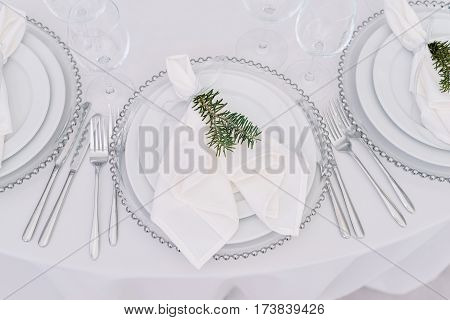 The cute exemple of wedding table serve with white napkin and setting with green fir twig