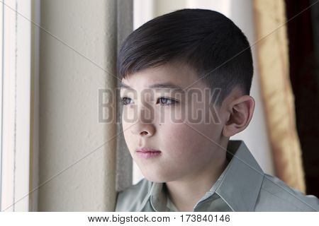 A young boy gazes out the window from inside.