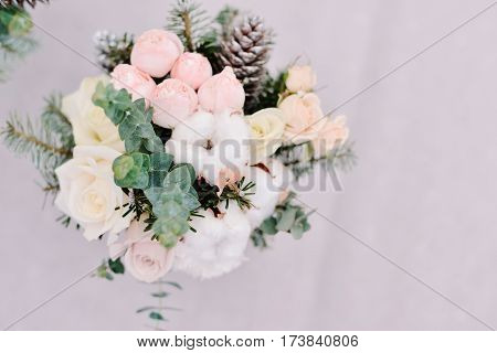 Tender wedding bouquet of roses, cone and cotton staying in front of silvery background, closeup
