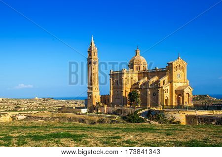 Gozo Malta - The Basilica of the National Shrine of the Blessed Ta' Pinu early at the morning with clear blue sky on a summer day