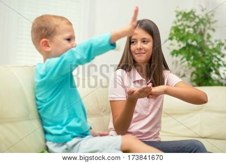 Brother and sister learn sign language at home. Deaf child
