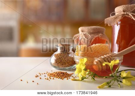 Honey Pots Honeycomb And Bee Pollen On White Kitchen Table