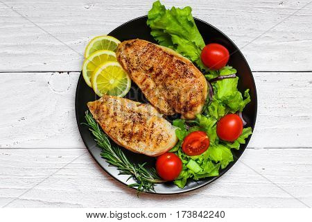 grilled chicken breast with green salad tomatoes lemon and rosemary on a black plate. top view