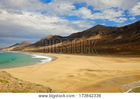 View on famous beach Playa de Cofete with mountains emerald ocean water yellow sand and blue sky with white clouds on the Canary Island Fuerteventura Spain.
