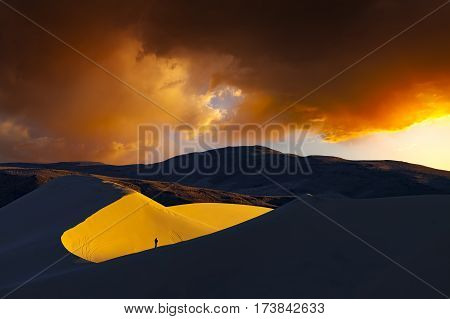 Sand dune at sunrise with photographer on edge of large bowl. Sand Mountain Fallon Nevada