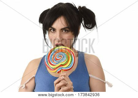 sexy and seductive woman with ponytails and blue top holding and licking sweet caramel big lollipop isolated in white background with naughty face expression