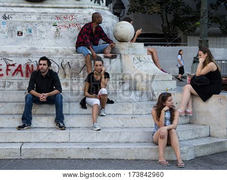 BELGRADE SERBIA - AUGUST 2 2015: People (young girls boys and an old man) waiting on Republic Square under the iconic horse Statue (Kod Konja)