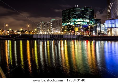 Modern illuminated business offices at night. Long reflections on the river from the lit windows and street lights. Tranquil water reflecting lights on its surface.