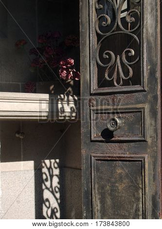 Rusted Door To Tomb With Flowers At Pere Lachaise Cemetery France