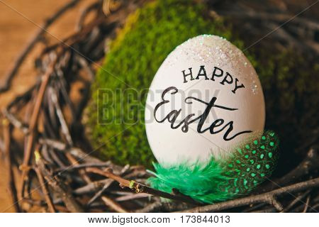 Beautiful Easter background with eggs in the nest and wishes for a happy Easter