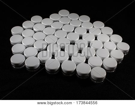 Small plastic jars with screwed on lids on black background