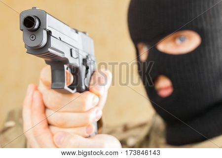 Man in mask holding gun in front of him